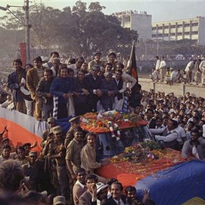 Mujibur Rahmen, standing at center in truck, is shown during motorcade from the airport to the sports stadium in Dacca, where an estmated 1 million people listened to him make an emotional speech, Jan. 11, 1972.  (AP Photo/Michel Laurent)